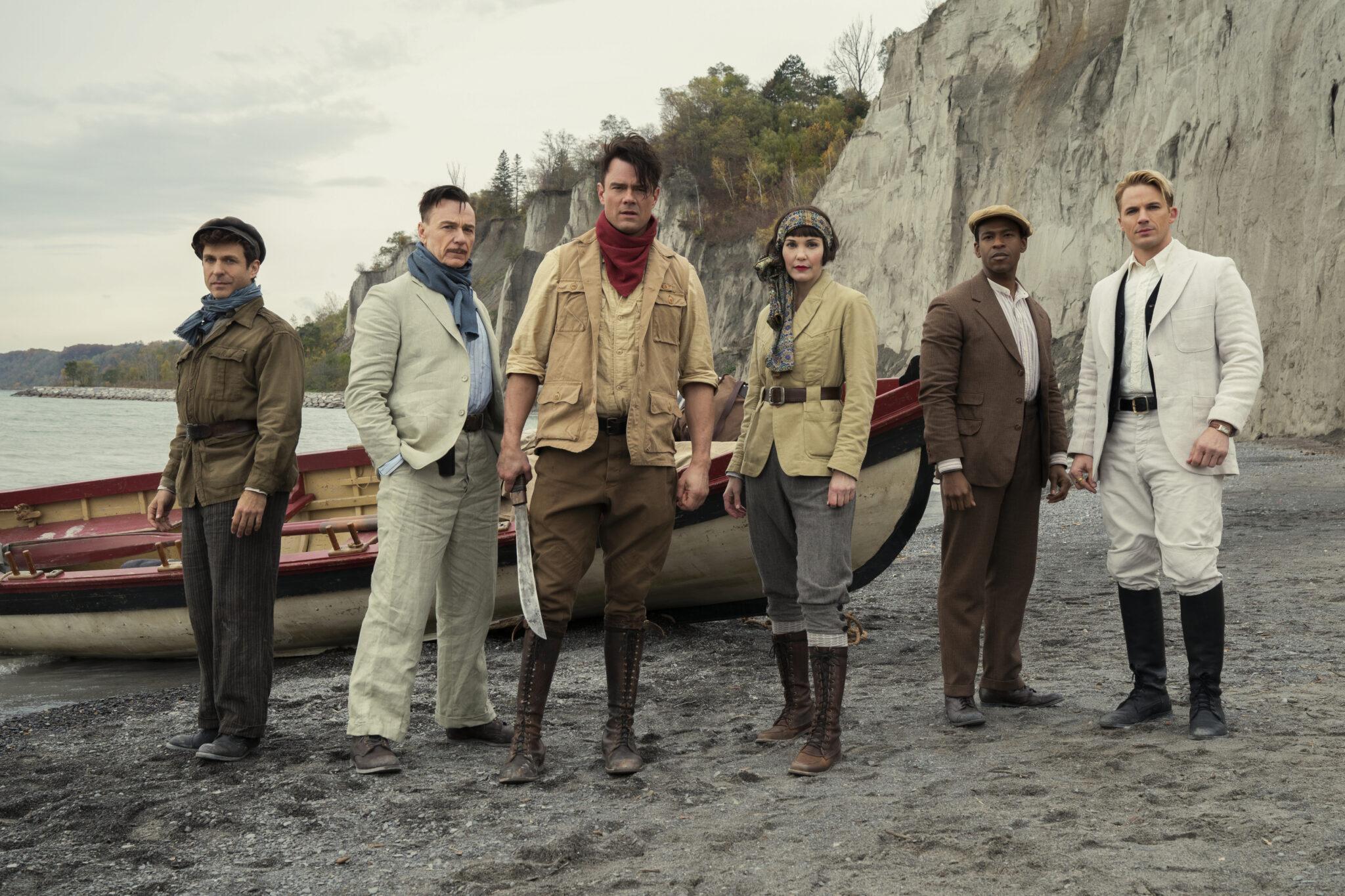 Fünf Personen stehen an einem Strand vor einem anlegenden Ruderboot und einer massiven Steilküste im Hintergrund. Sie tragen alle typische Abenteurerkluft und der Mann in der Mitte hält eine Machete in seiner rechten Hand.