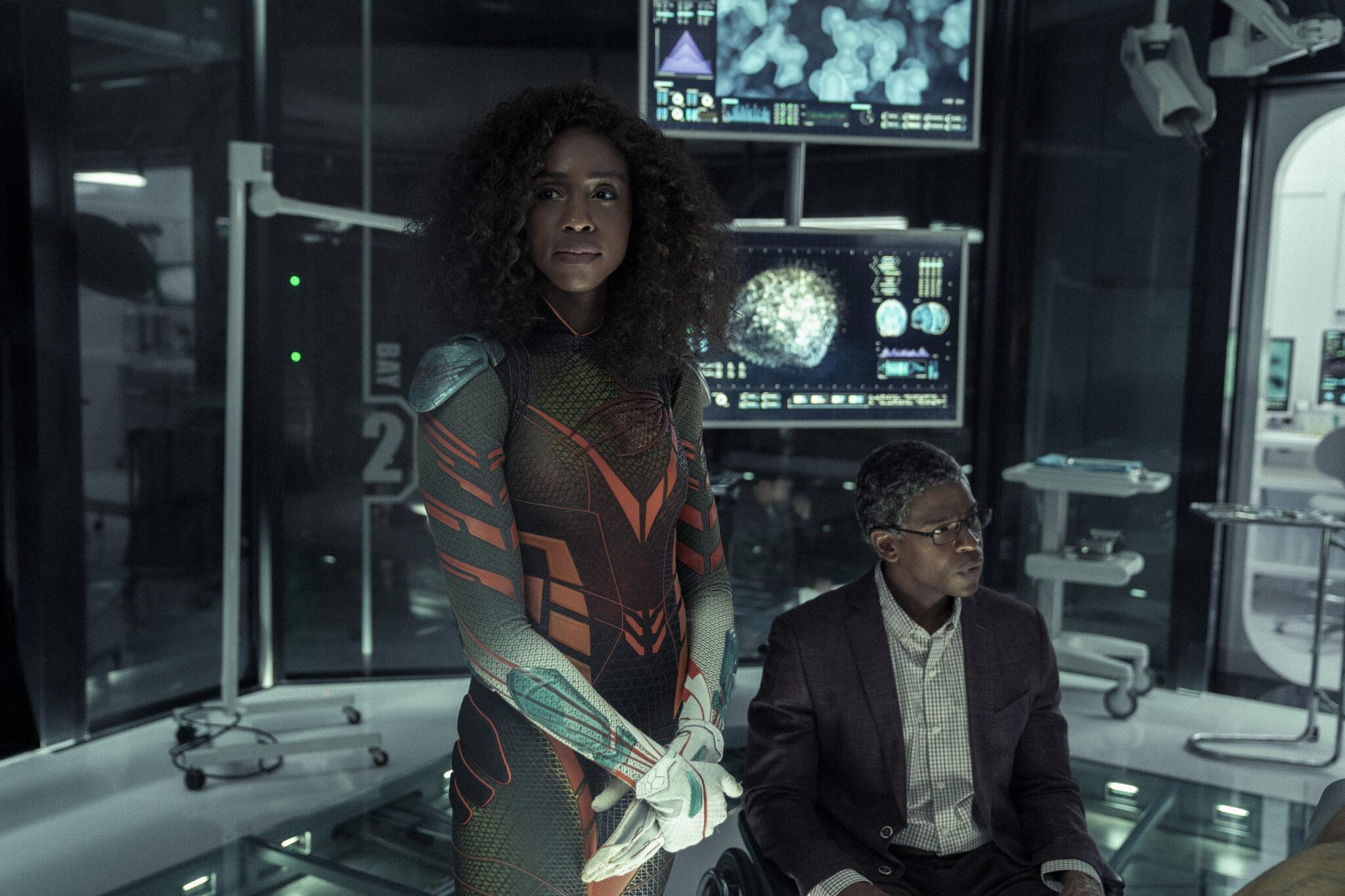 Petra Small und Fitz Small in einem Labor mit Apparaturen und Bildschirmen im Hintergrund. Sie trägt ein enges Heldenkostüm, er sitzt mit Anzug im Rollstuhl rechts neben ihr.