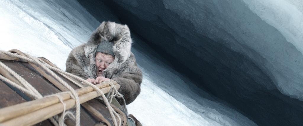 Entdecker hält sich an einem Schlitten fest und droht, in Eisspalte zu fallen in Amundsen - Wettlauf zum Südpol