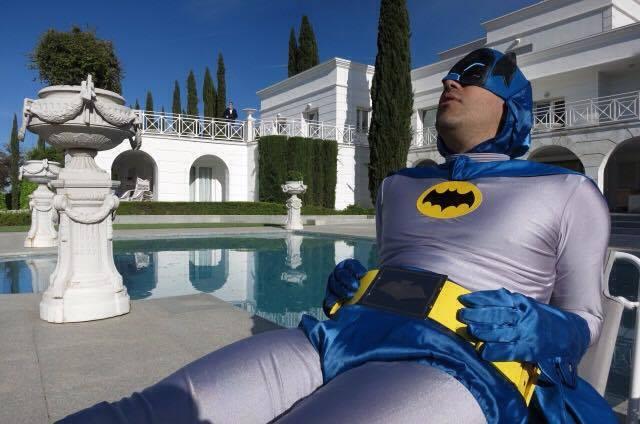 Ein Mann im Batman-Kostüm fletzt sich im Liegestuhl am Pool seiner Villa - Jesus Shows You the Way to the Highway