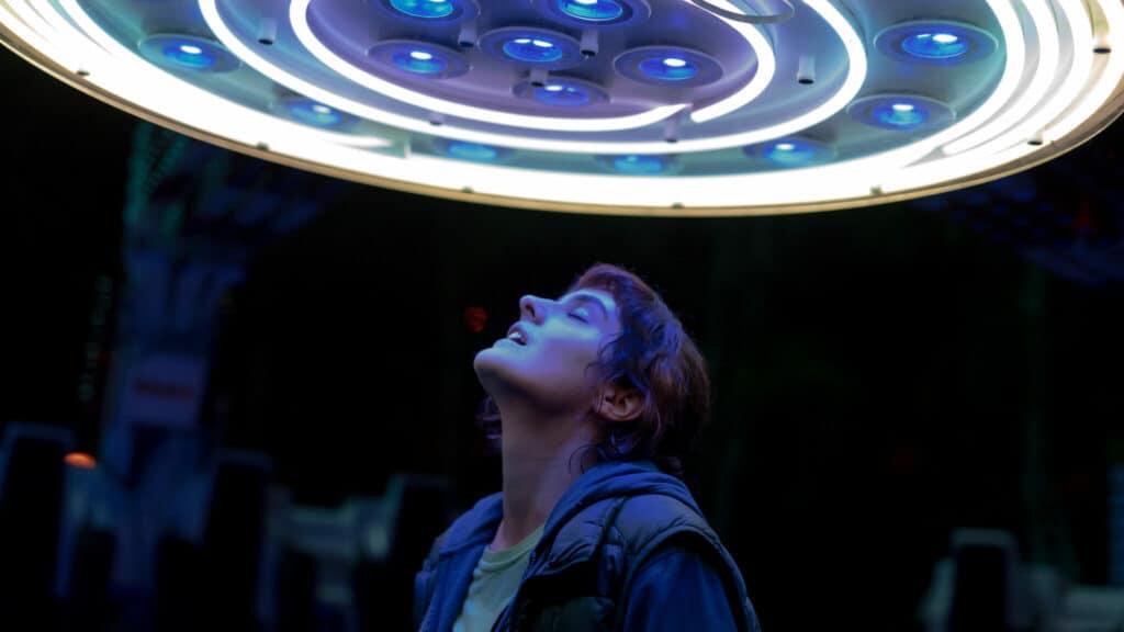 Jeanne (Noémie Merlant) spurt die Energie von JUMBO, der Freizeitparkattraktion, deren Lichter über ihrem Kopf leuchten.