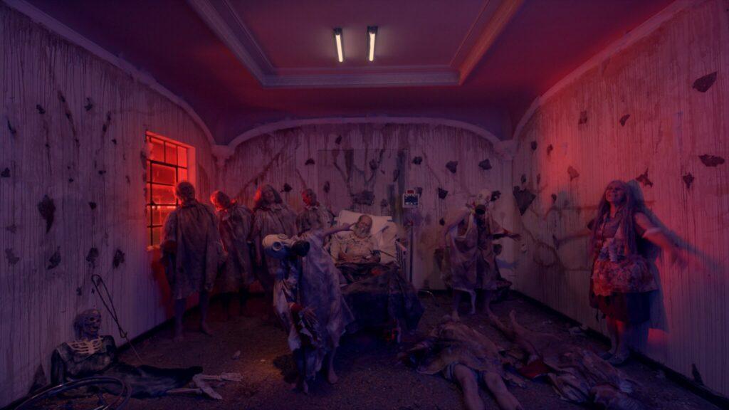 Mittig im Bild ist ein schwer erkrankter Koma-Patient positioniert. Er liegt auf seinem Krankenbett. Zu seiner linken ist ein Monitor für die Überwachung der Herzfrequenz aufgestellt. Um ihn herum sind Zombies, die teilweise Gasmasken tragen und unterschiedlich verweste Leichen auf dem Boden. Im Bild dominieren violette und pinke bis rote Farbtöne.