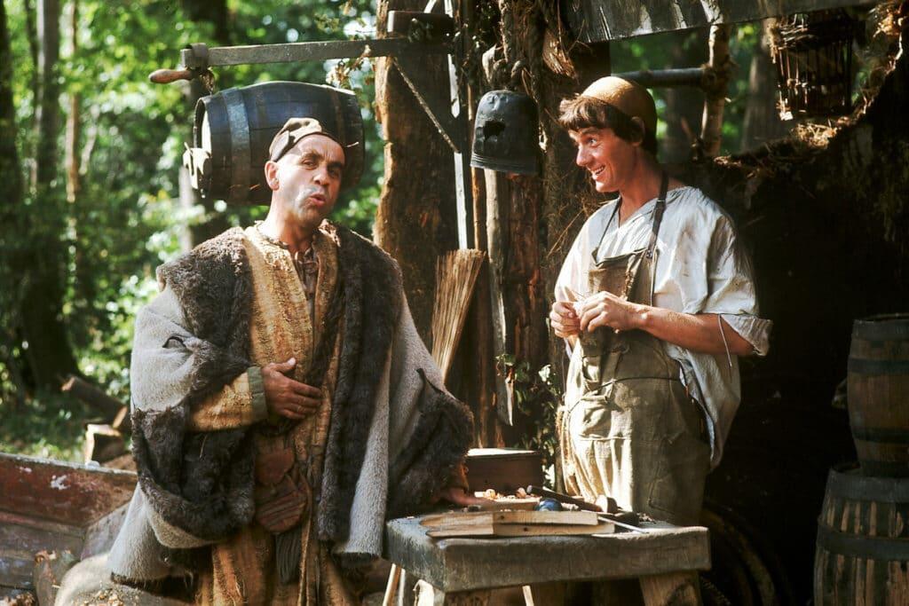 Michael Palin als Dennis mit Warren Mitchell als Mr. Fishfinger im Gespräch im Fischhandel. An einem Holzverschlag hängen diverse Utensilien wie ein Fass oder ein Helm.