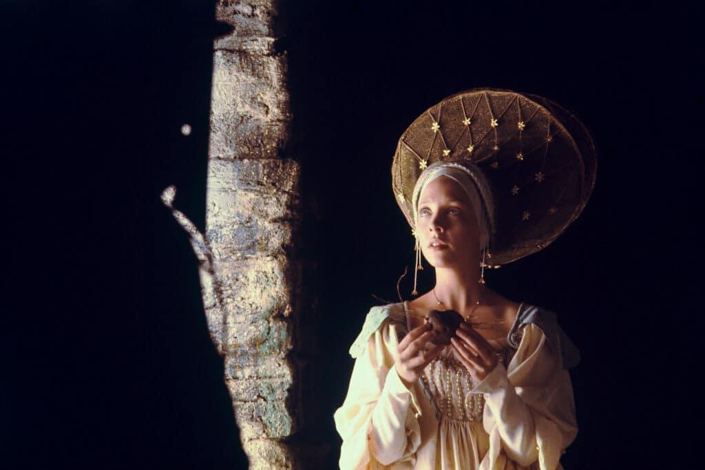 Deborah Fallender steht als Prinzessin in Jabberwocky in der Dunkelheit. Neben einem Kleid trägt sie einen extravaganten Hut.
