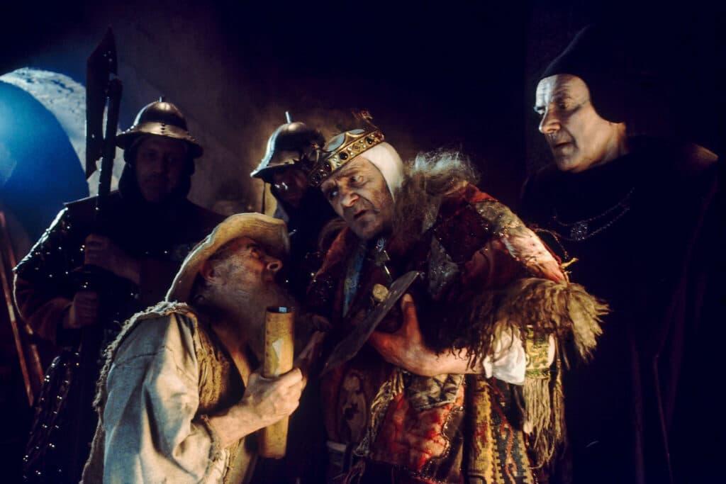 Max Wall ist in Jabberwocky als König Bruno der Fragwürdige umringt von zwei Wachen und einem Berater. Er lauscht aufmerksam den Worten eines Bürgers, der vor ihm kniet.
