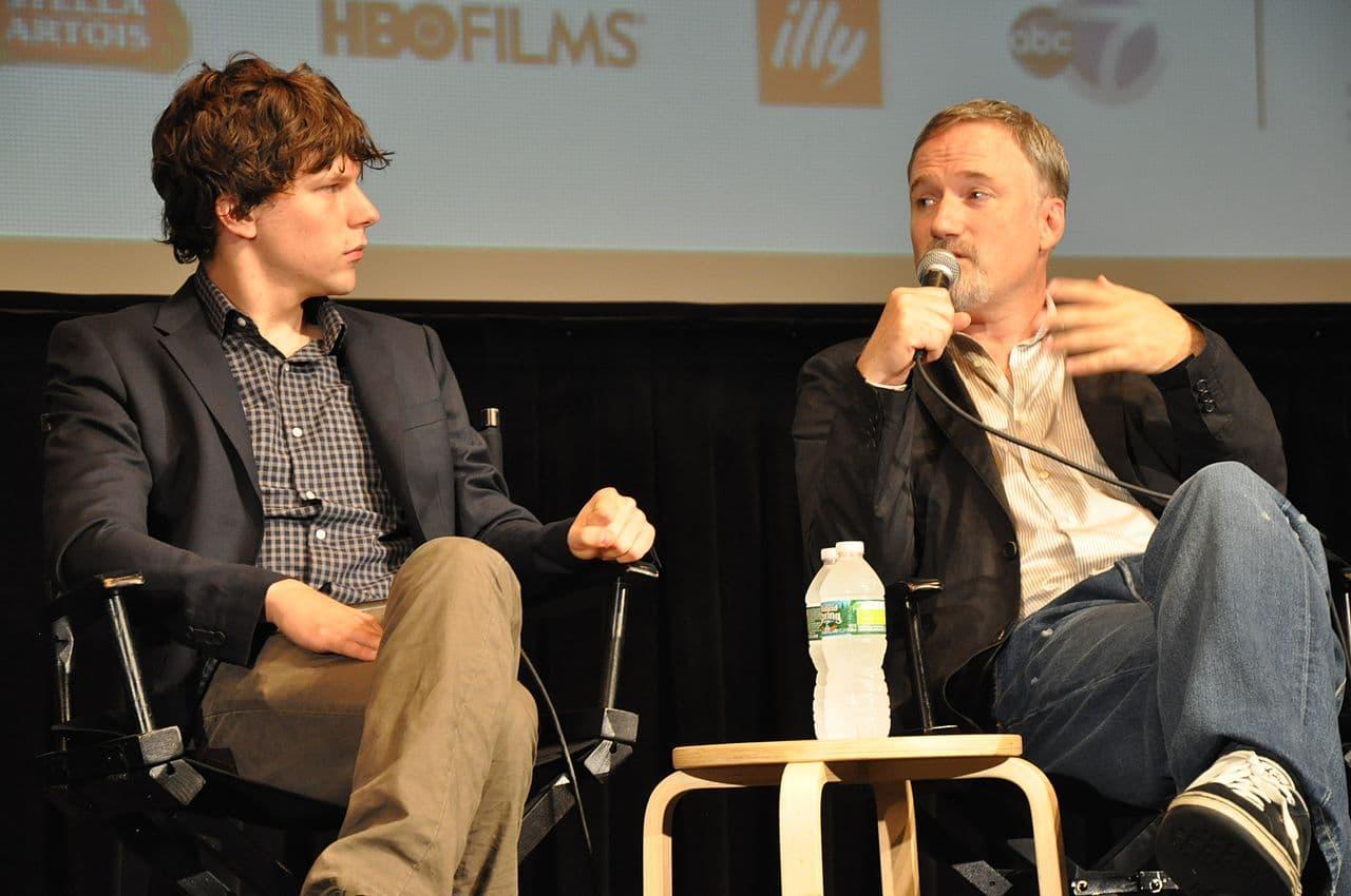 Jesse Eisenberg und David Fincher sitzen in Klappstühlen mit verschränkten Beinen vor einer Leinwand. Fincher hat ein Mikrofon in der einen Hand und gestikuliert mit der anderen.