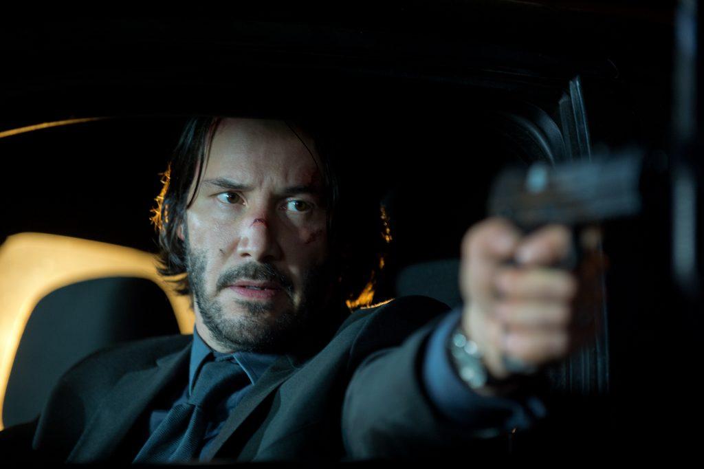 Keanu Reeves als John Wick im Auto mit erhobener Pistole