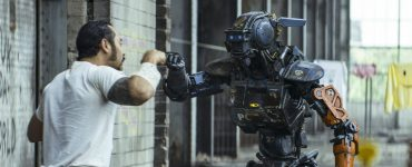 Jose Pablo Cantillo als Yankie bringt Chappie die Grundlagen des Lebens bei in CHAPPIE (2015) © 2015 Columbia Pictures Industries, Inc., LSC Film Corporation and MRC II Distribution Company L