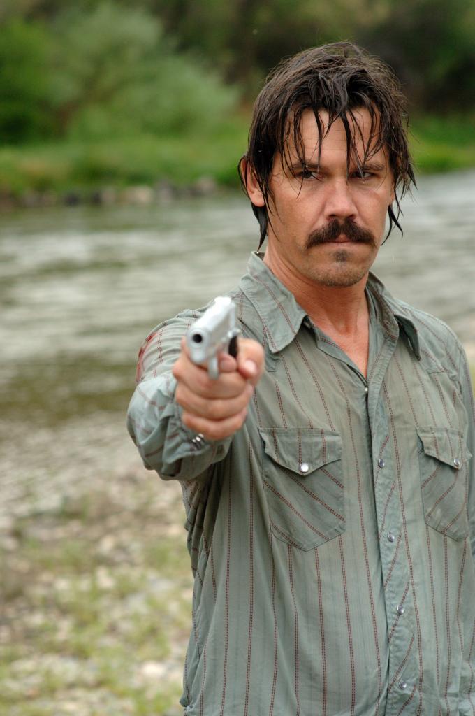 Josh Brolin als Llewlyn Moss, durchnässt an einem Fluss, richtet eine Waffe auf sein Gegenüber