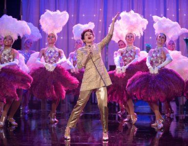 Judy auf der Bühne in London. Um sie herum sind mehrere Tänzerinnen mit rosarotem Federschmuck.