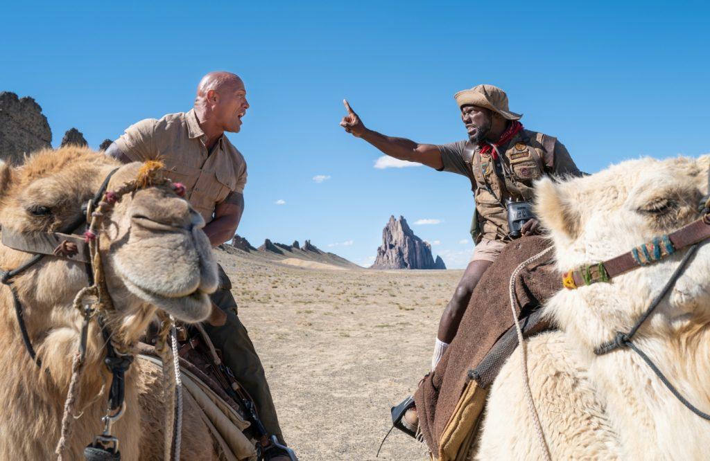 Eddie (Dwayn Johnson/Danny DeVito) und Milo (Kevin Hart/Danny Glover) streiten sich in Jumanji: The Next Level auf ihren Kamelen