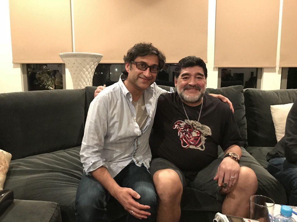 Diego Maradona und Asif Kapadia sitzen auf einem Sofa und lächeln in die Kamera