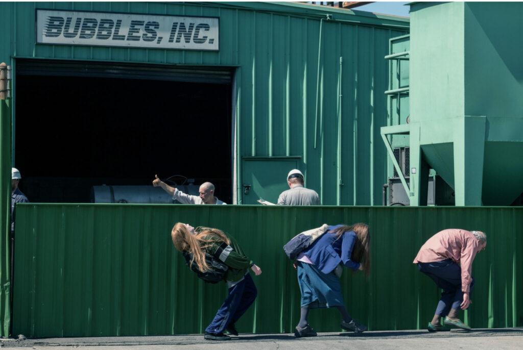 Die Betrügerfamilie aus Kajillionaire versucht sich vor ihrem Vermieter zu verstecken, um die rückständige Miete nicht bezahlen zu müssen. Dabei gehen sie stark gekrümmt in einer Reihe, sodass sie von einem Industriezaun verdeckt werden.