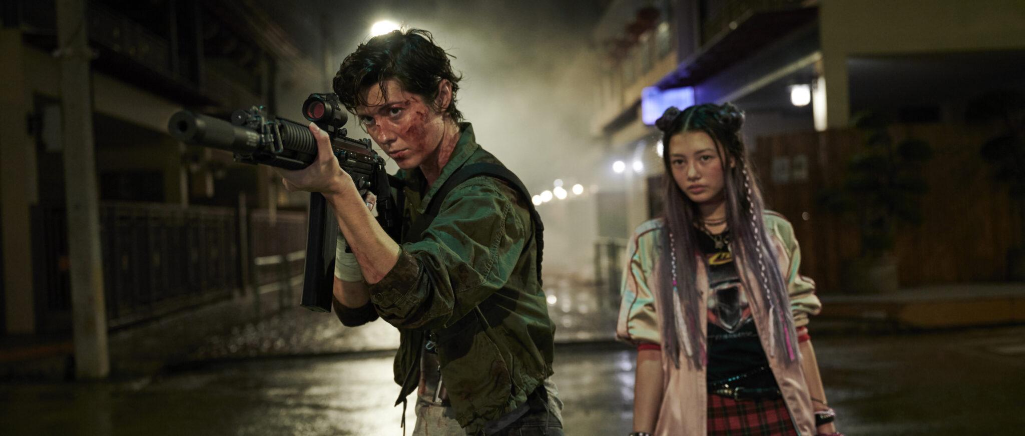 Mary Elizabeth Winstead als Titelfigur Kate mit grüner Jacke, blutverschmiertem Gesicht und Sturmgewehr im Anschlag. Rechts neben ihr steht in einer dunklen Gasse Miku Martineau mit buntem Outfit.