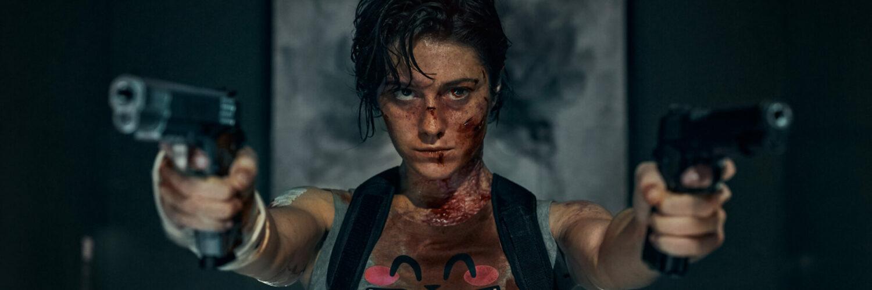Kate mit entschlossener Miene und zwei Pistolen von sich gestreckt.