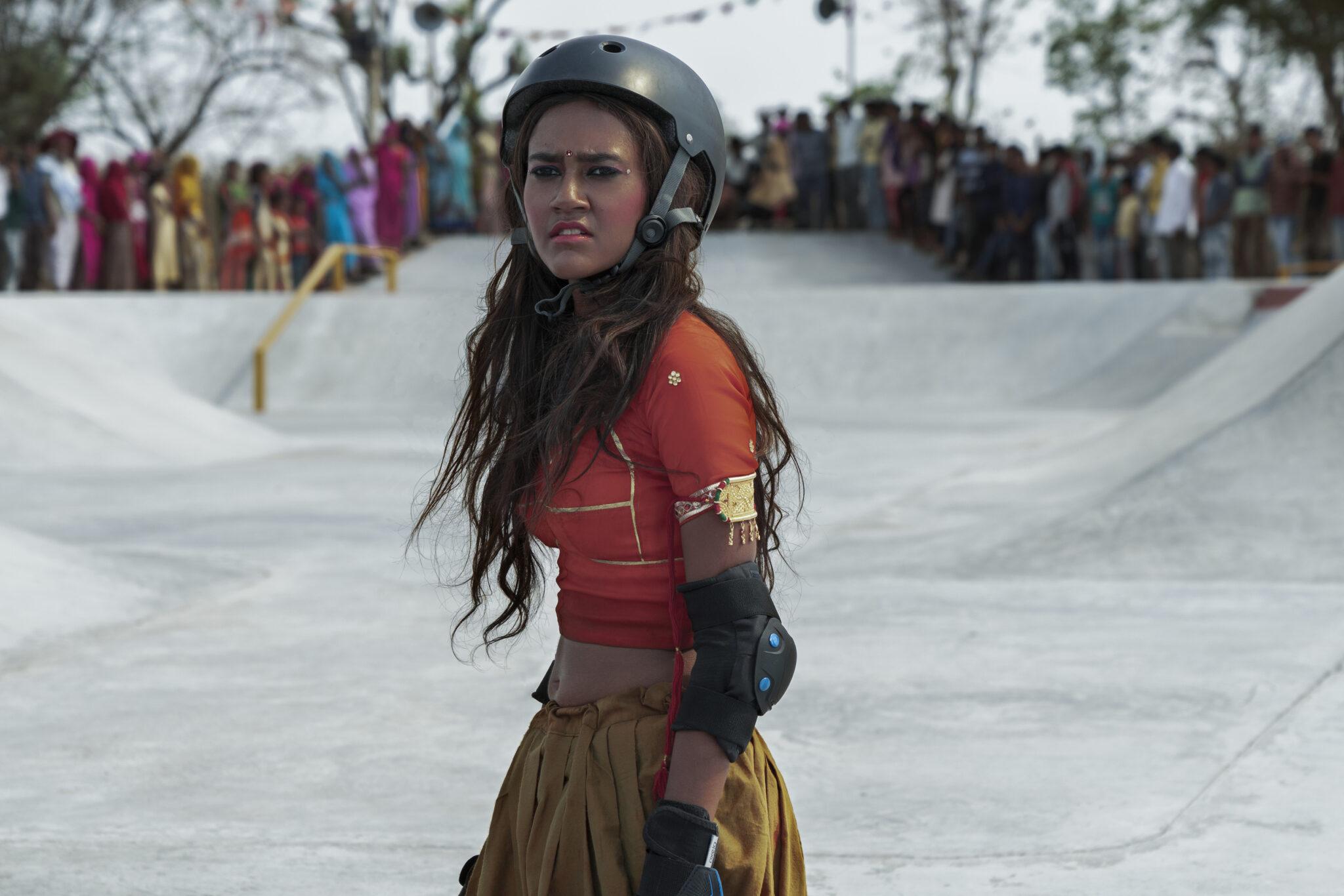 Prerna (Rachel Saanchita Gupta) steht in einem Skatepark mit rotem Oberteil und schwarzem Helm. Im Hintergrund sieht man verschwommen zahlreiche Zuschauer.