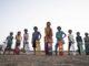 Die Jugendlichen des indischen Dorfes stehen nebeneinander jeweils mit Helm und Skateboard in der Hand.