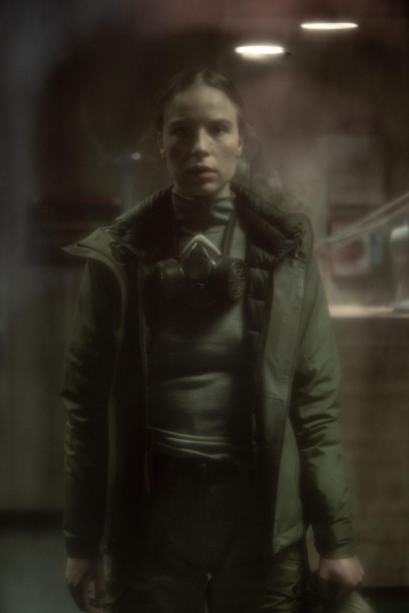 """Das verschwommene Bild zeigt die Protagonistin von """"Katla"""" Gríma in einem Oliven Parka mit einer Gasmaske um den Hals und leerem Gesichtsausdruck."""