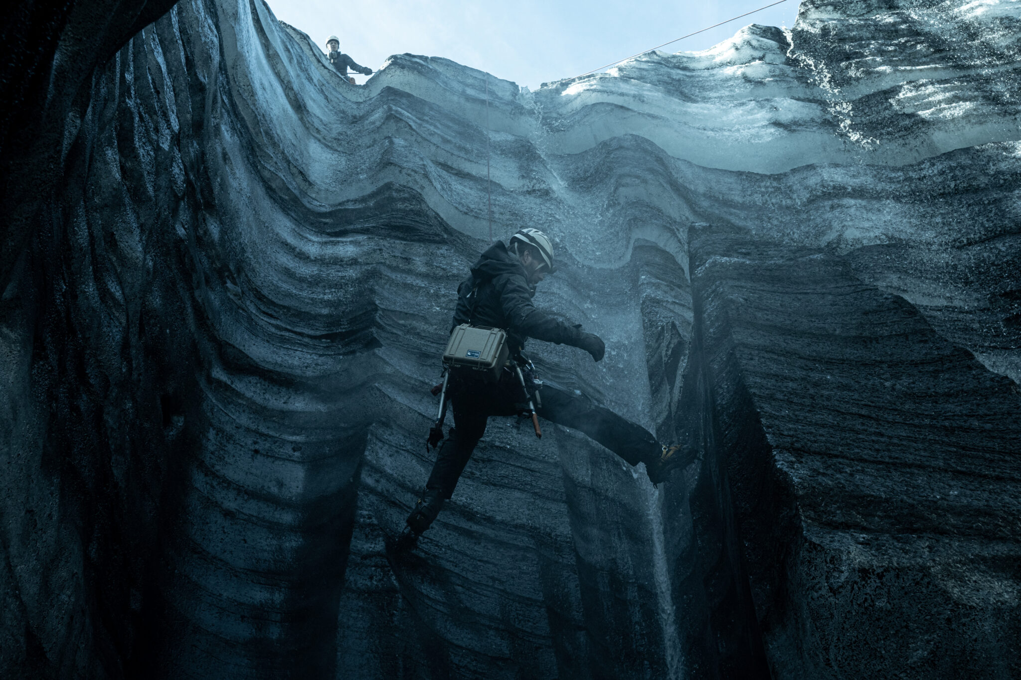 Man sieht einen tiefen Krater, in den von oben ein Mann mit Werkzeugen an einem Seil herabgelassen wird.