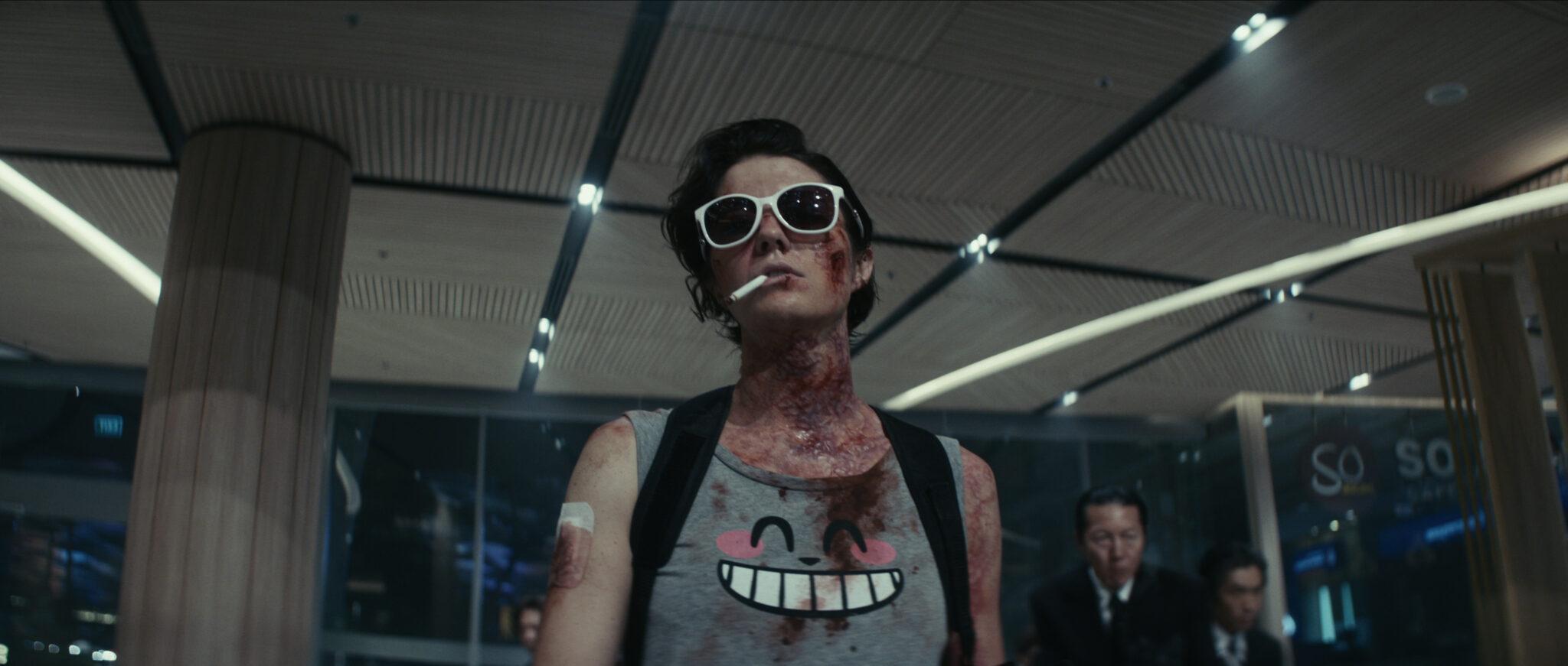 Mary Elizabeth Winstead voll mit Blut, mit Zigarette im Mund und Sonnenbrille. Außerdem trägt sie ein Tanktop mit grinsendem Katzen-Print. Sie steht in einem Büroraum unter Neonröhren und hinter ihr sieht man mehrere Anzugträger