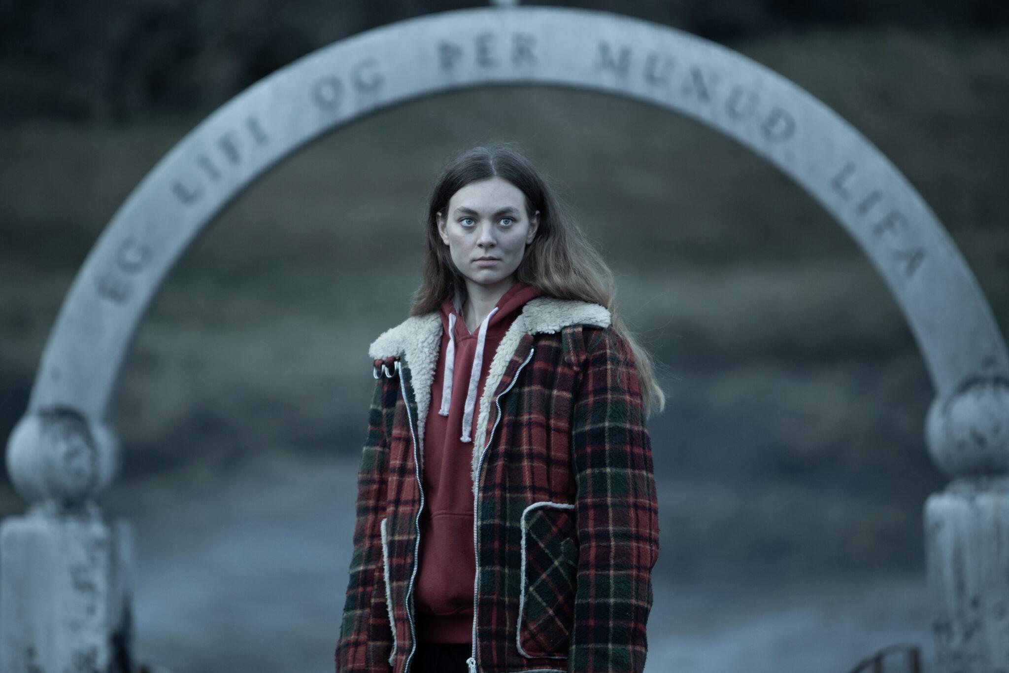 Åsa steht mit einer karierten Jacke und rotem Hoodie vor einem Torbogen.