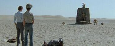 Die beiden Hauptfiguren Vladimir und Gedewan stehen am linken Bildrand in einer kargen Wüstenlandschaft. Um sie herum ist nur Sand zu sehen, direkt vor Ihnen auf dem Boden liegt ihr Handgepäck. Im Hintergrund ist ein glockenförmiges Raumschiff gelandet, aus dem ein menschenähnliches Wesen ausgestiegen ist, in die Hocke geht und eine merkwürdige Verbeugung durchführt. Er trägt dreckige sandfarbene Kleidung. Im Raumschiff steht auf einer ausfahrbaren Rampe ein Käfig mit einem weiteren Außerirdischen darin, der ebenfalls in die Hocke geht und diesen merkwürdigen Gruß ausführt. © 1986 Mosfilm