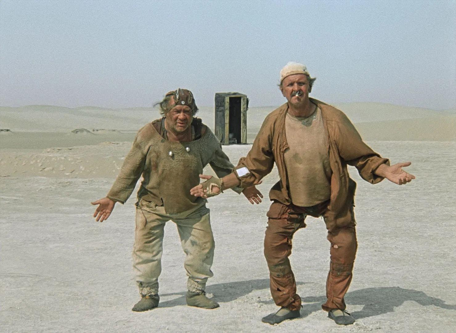 In dieser Szene von Kin-Dza-Dza stehen die beiden menschenähnlichen Außerirdischen Uef und Bi im Vordergrund einer kargen Wüstenlandschaft. Sie tragen beide sandfarbene, dreckige und einfache Kleidung. Beide gehen leicht in die Hocke und strecken die Arme wie Flügel von sich.