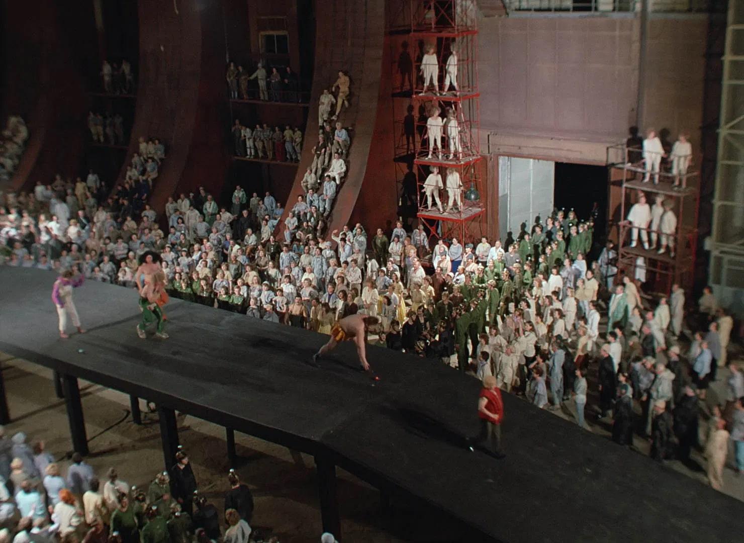 In der Szene aus Kin-Dza-Dza stehen sehr viele Menschen in mehreren Reihen nebeneinander in einem großen Raum. Alle tragen verschiedenfarbige Arbeitskleidung. In der Mitte des Raumes ist ein schwarzer Laufsteg, auf dem mehrere Personen herumlaufen. Die Wände des Raumes sind teilweise mit abgerundeten roten Metallsäulen gestützt, an deren Seite kleine Podeste angebracht sind, auf denen auch Menschen in Arbeitskleidung stehen.