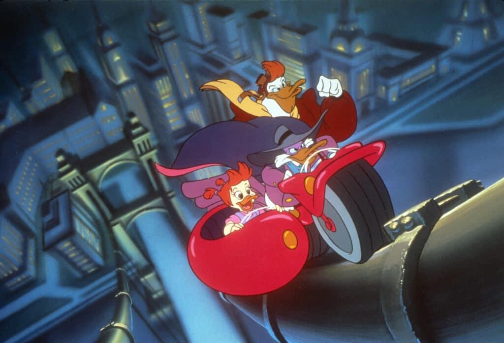 Darkwing Duck und seine Gefährten (Töchterchen Kiki und Kumpane Quack) zählen zu den bekanntesten Kinderserien der 90er. Die drei fahren mit dem Motorrad die Aufhängung einer riesigen Brücke hinauf.