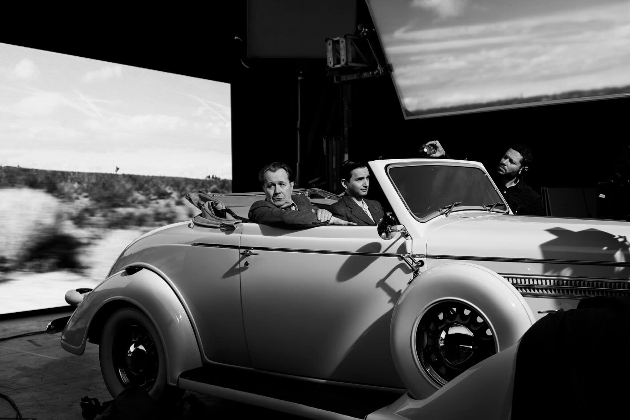 Herman J. Mankiewicz (Gary Oldman) sitzt in einem weißen Oldtimer an einem Filmset vor einer Leinwand.