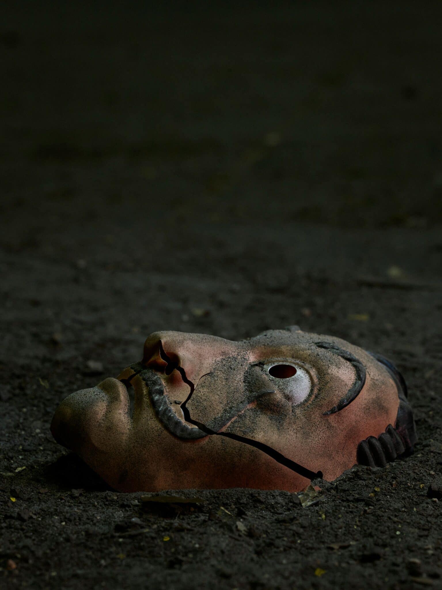 Eine Dali-Maske liegt verschmutzt auf dem staubigen Boden.