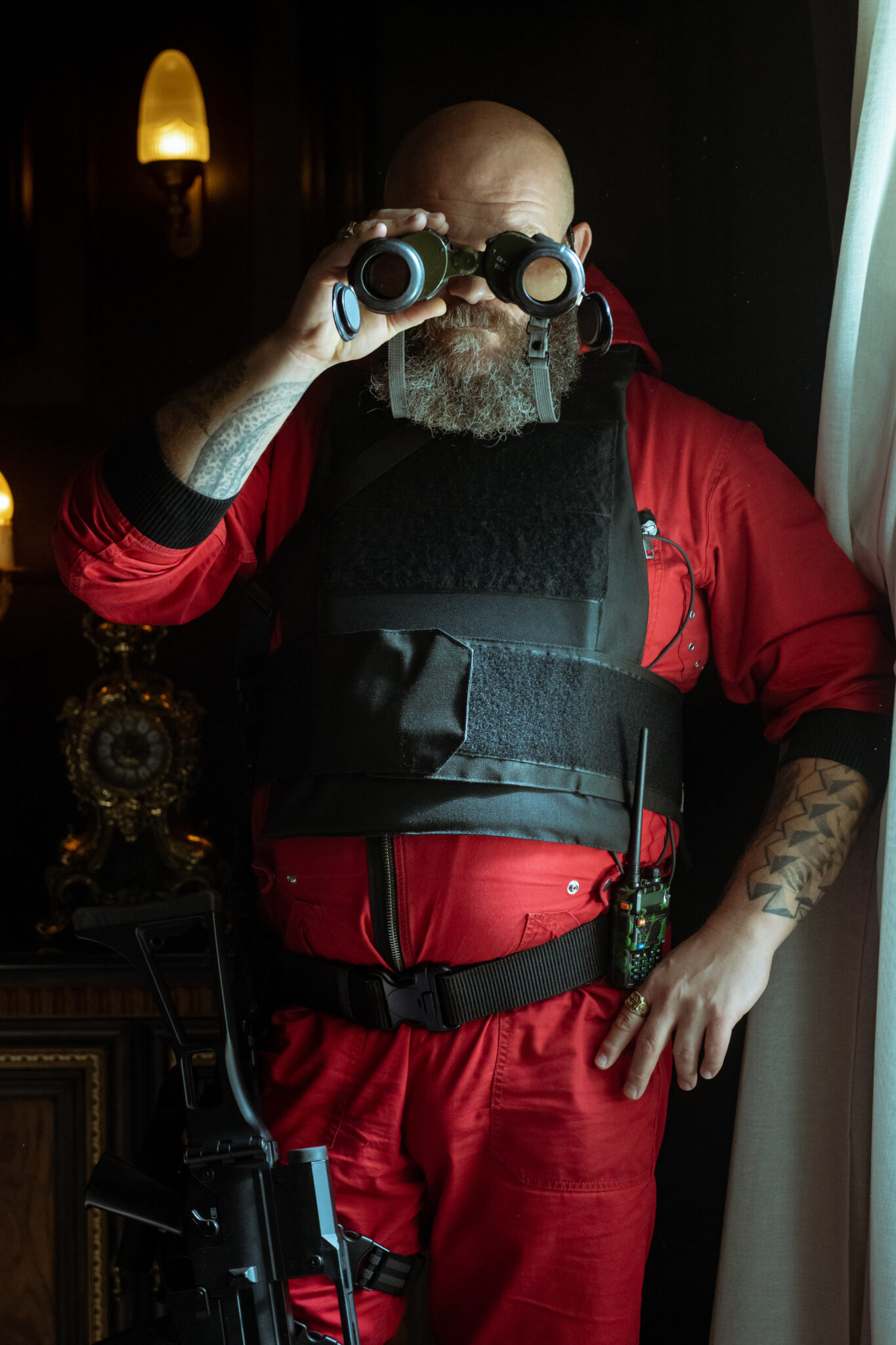 Helsinki (Darko Peric) in rotem Overall und Schutzweste gekleidet mit einem Feldstecher vor dem Gesicht.