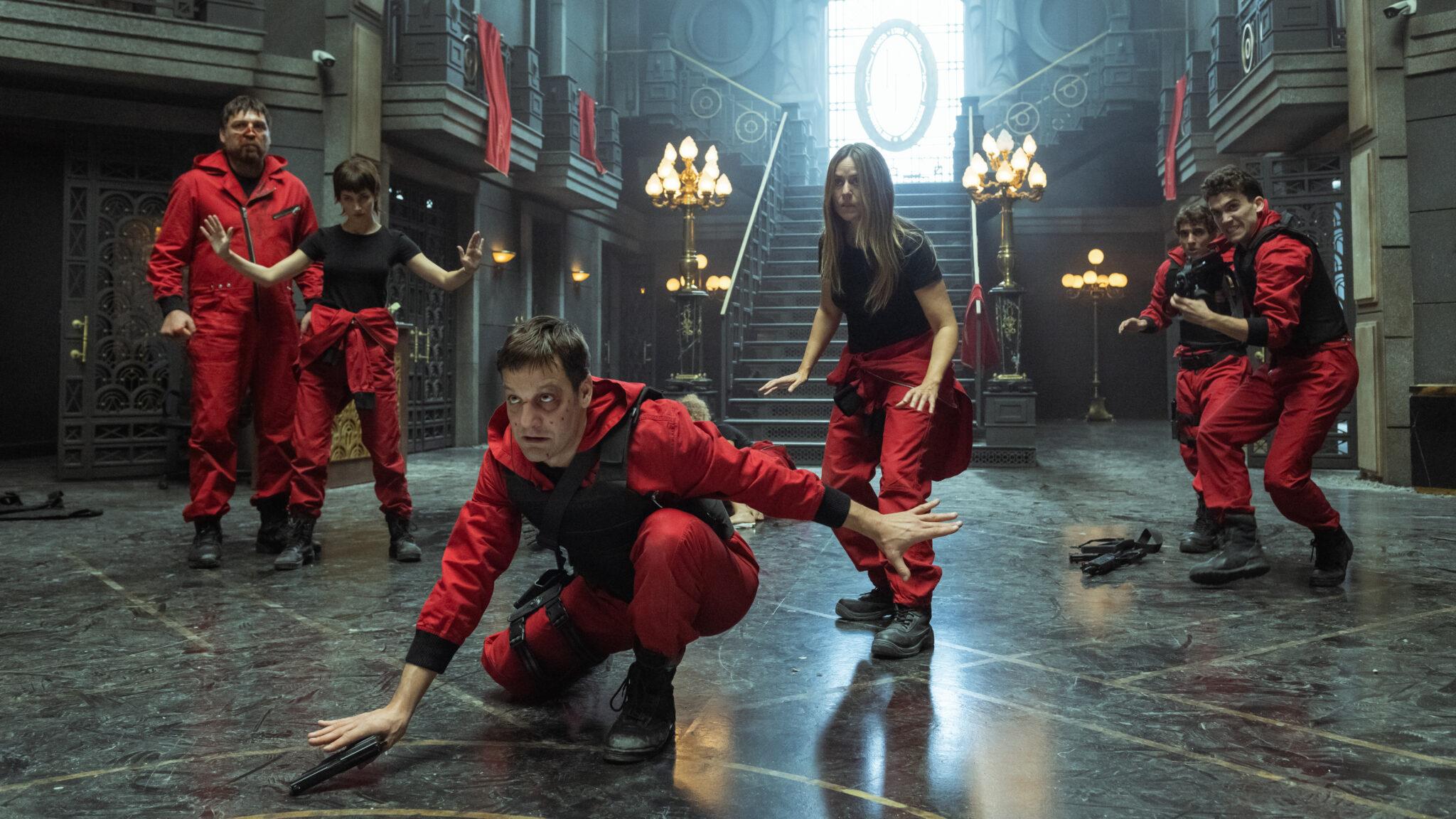 Man sieht 6 Mitglieder der Diebesbande aus Haus des Geldes in ihren ikonischen roten Overalls im Foyer des Bankgebäudes.