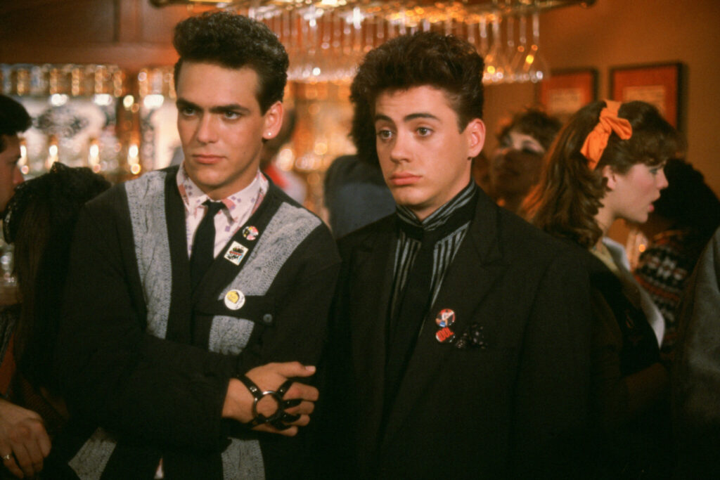 """Robert Rusler und Robert Downey Jr.spielen in """"L.I.S.A. - Der helle Wahnsinn"""" die beiden Mobber. Beide stehen nebeneinander, Rusler links und Downey Jr. rechts. Rusler ist gekleidet mit einer schwarz-grauen Jacke, Krawatte und einer Art Lederband um die rechte Hand. Er steht mit verschränkten Armen und blickt selbstsicher auf etwas außerhalb des Bildes. Downey Jr. trägt ein schwarzes Sakko und ebenfalls eine Krawatte. Auch er blickt in dieselbe Richtung, aber sein Gesichtsausdruck zeigt Verblüffung, denn seine Augenbrauen sind hochgerissen und seine Augen weit geöffnet."""