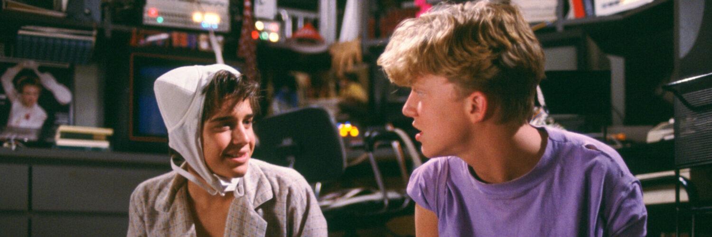 Wyatt (Ilan Mitchell-Smith) und Gary (Anthony Michael Hall) bereiten die Zeremonie vor. Beide sitzen im Schneidersitz auf dem Fußboden und schauen sich an. Gary, rechts im Bild, trägt ein lila T-Shirt und hält in der Hand eine Barbie-Puppe, die später zu Lisa wird. Wyatt trägt ein Hemd und auf dem Kopf einen weißen BH. In der Hand hält er ein Buch.