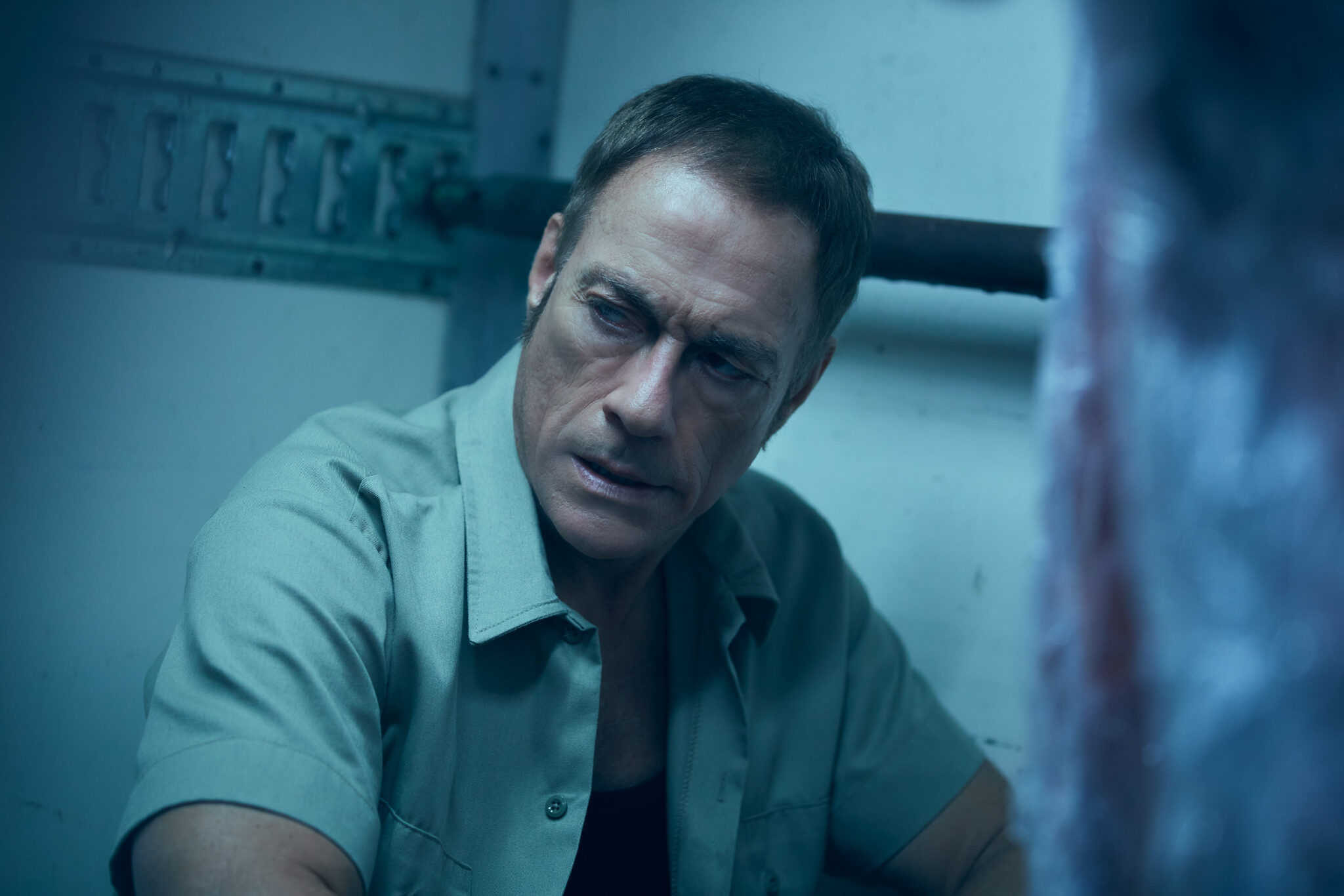Jean-Claude Van Damme mit ernstem Gesichtsausdruck in einem grauen Kurzarmhemd