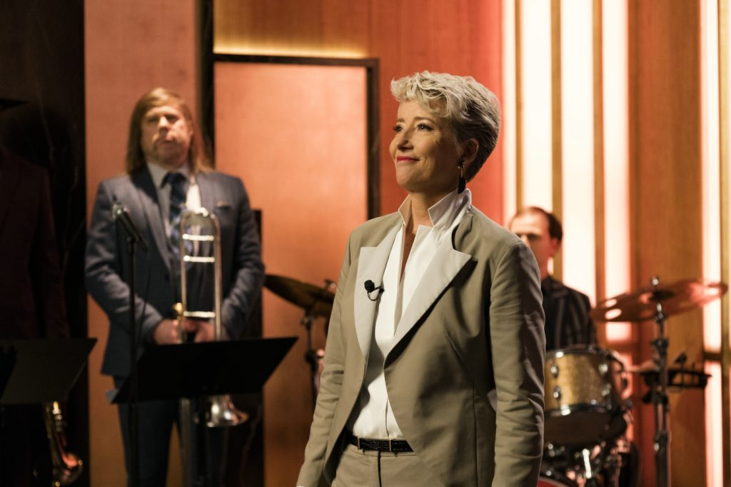 Die Moderatorin verabschiedet sich am Ende ihrer Show von dem Publikum. Im Hintergrund ist ihre Studio Band zu sehen.