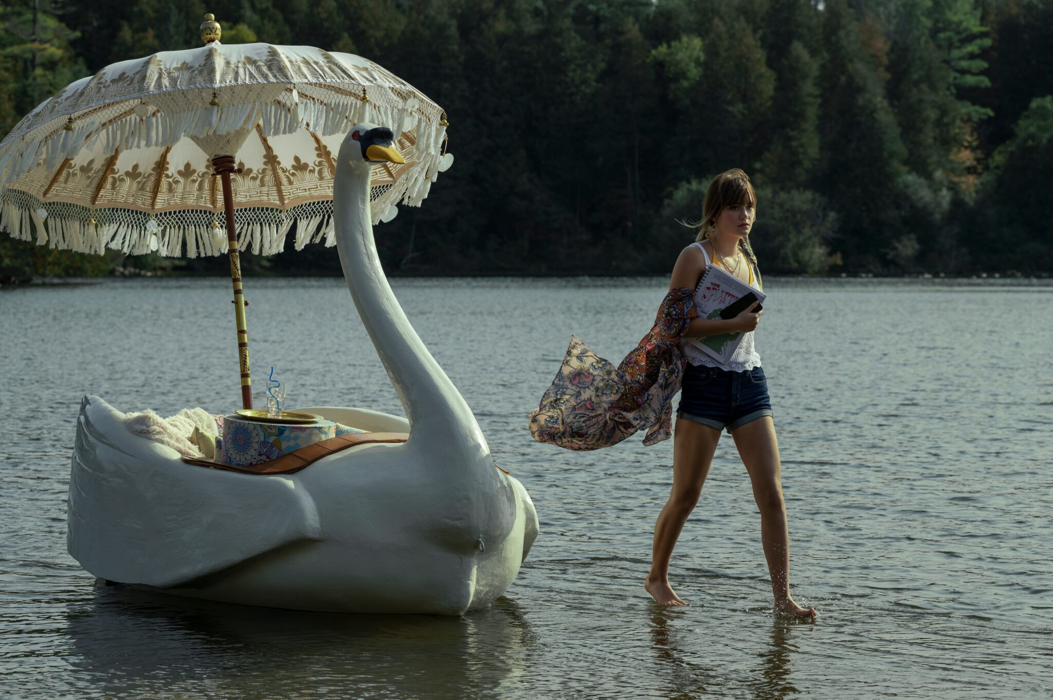 Emilia Jones läuft übers Wasser. Neben ihr sieht man ein Boot in Form eines Schwans mit Schirm.