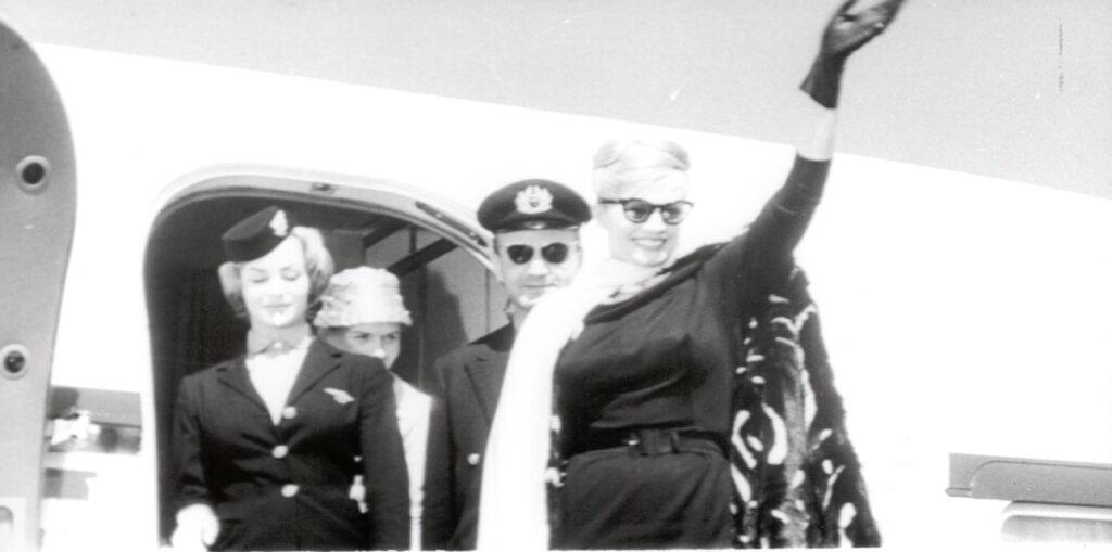 Sylvia, gespielt von Anita Ekberg, wirft sich in La dolce vita nach der Landung in Rom für die wartenden Fotoreporter in Pose.