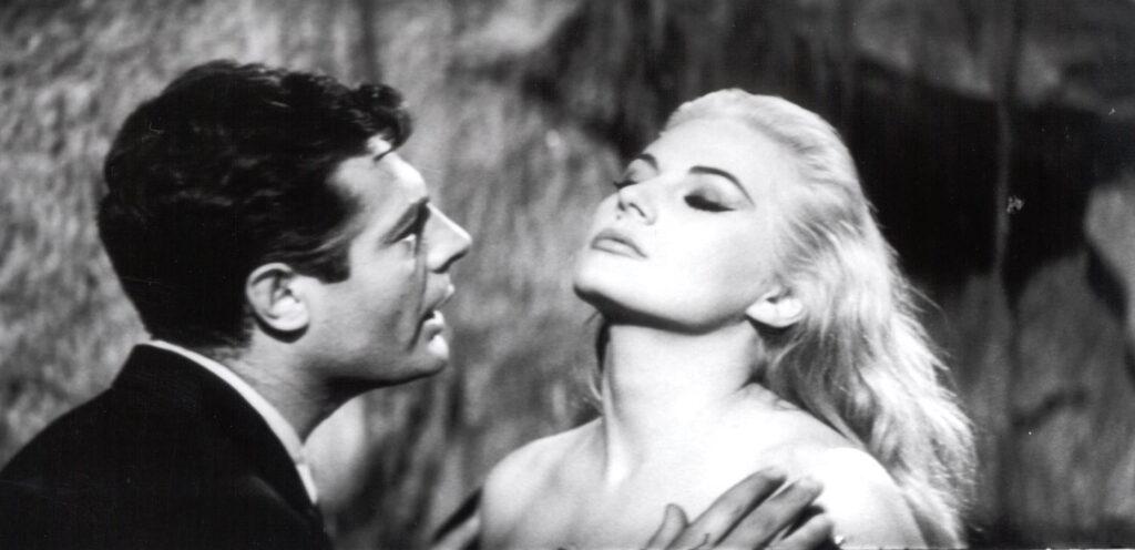 Marcello, gespielt von Marcello Mastroianni, steht kurz davor, Sylvia, gespielt von Anita Ekberg, im Trevi-Brunnen zu küssen.
