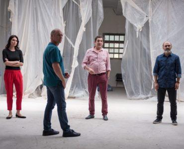 Der korrupte Polizist Cristi, die Femme fatale Gilda und drei weitere Gangster stehen in einer leeren Lagerhalle und fixieren einen Punkt außerhalb des Bildes an.
