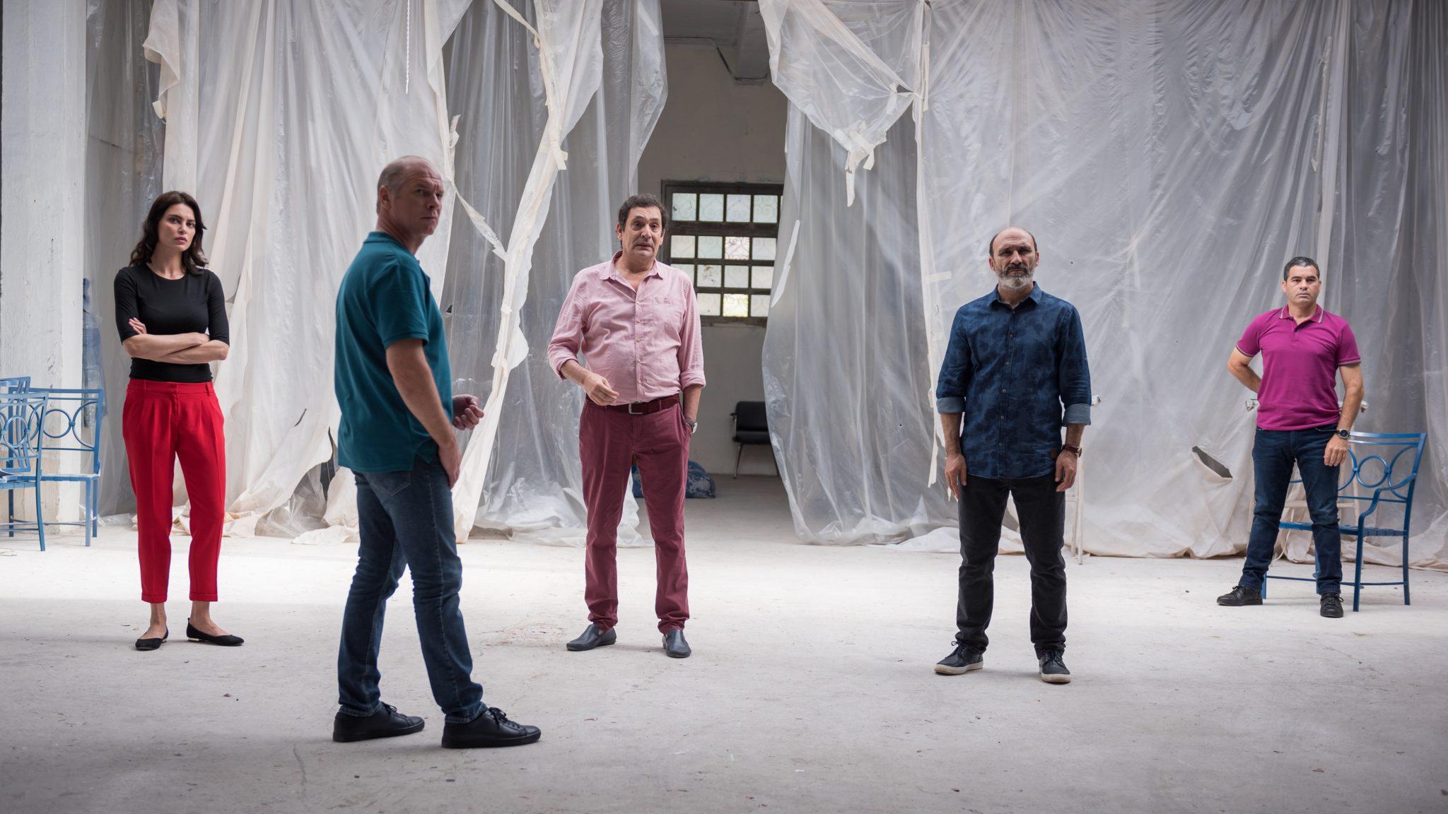 Der korrupte Polizist Cristi, die Femme fatale Gilda und drei weitere Gangster stehen in einer leeren Lagerhalle auf der Insel La Gomera und fixieren einen Punkt außerhalb des Bildes an.