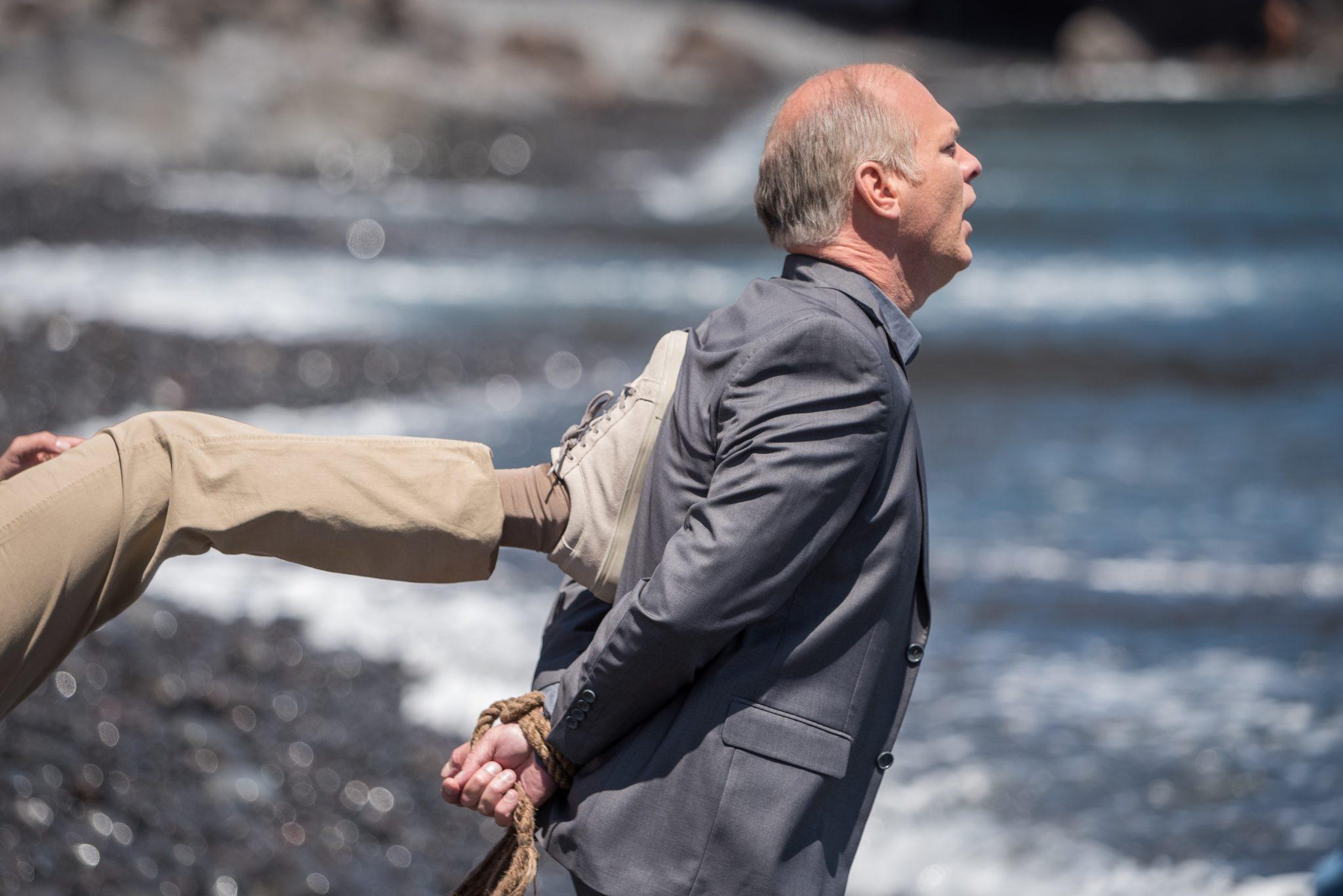 Cristi wird auf der Insel La Gomera von einem Gangster ins Meer getreten. Die Person ist nicht zu sehen, nur sein Bein, das Cristi am Rücken trifft, ist im Bild.