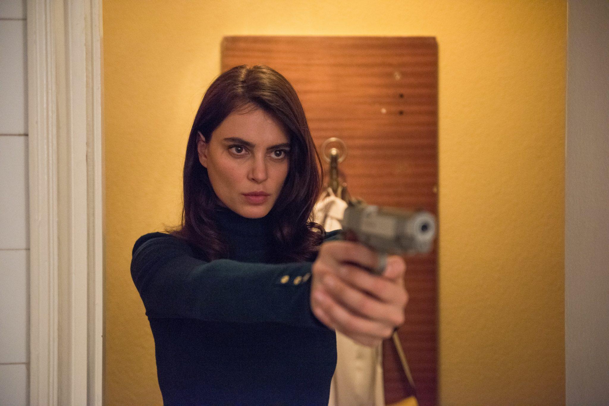 Gilda steht in einem gelben Hotelzimmer und visiert mit einer Pistole jemanden außerhalb des Bildbereichs an. Nicht zuletzt ihr bestimmter Gesichtsausdruck zeigt: Sie ist die Femme fatale in La Gomera.