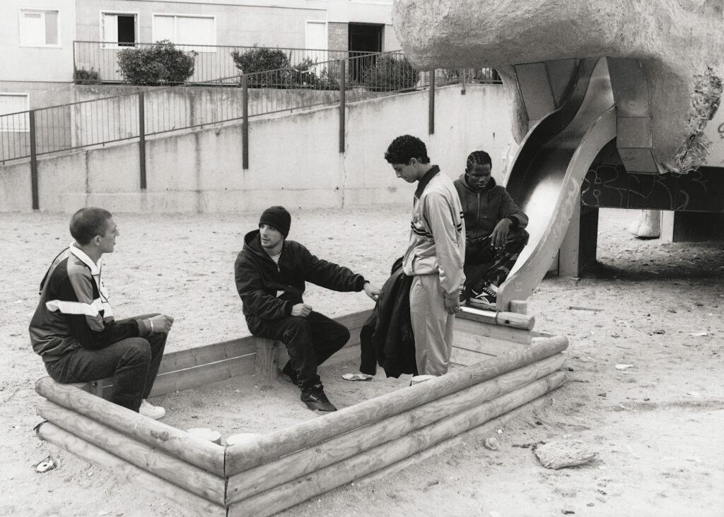 Mathieu Kassovitz sitzt mit Vincent Cassel, Said Taghmaoui und Hubert Kuondé in einem Sandkasten und erklärt ihnen die Szene - Hass