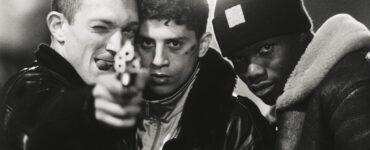 Die Freunde Vinz, Said und Hubert stehen zusammen und Vinz ziel mit einer Waffe in die Kamera - Hass