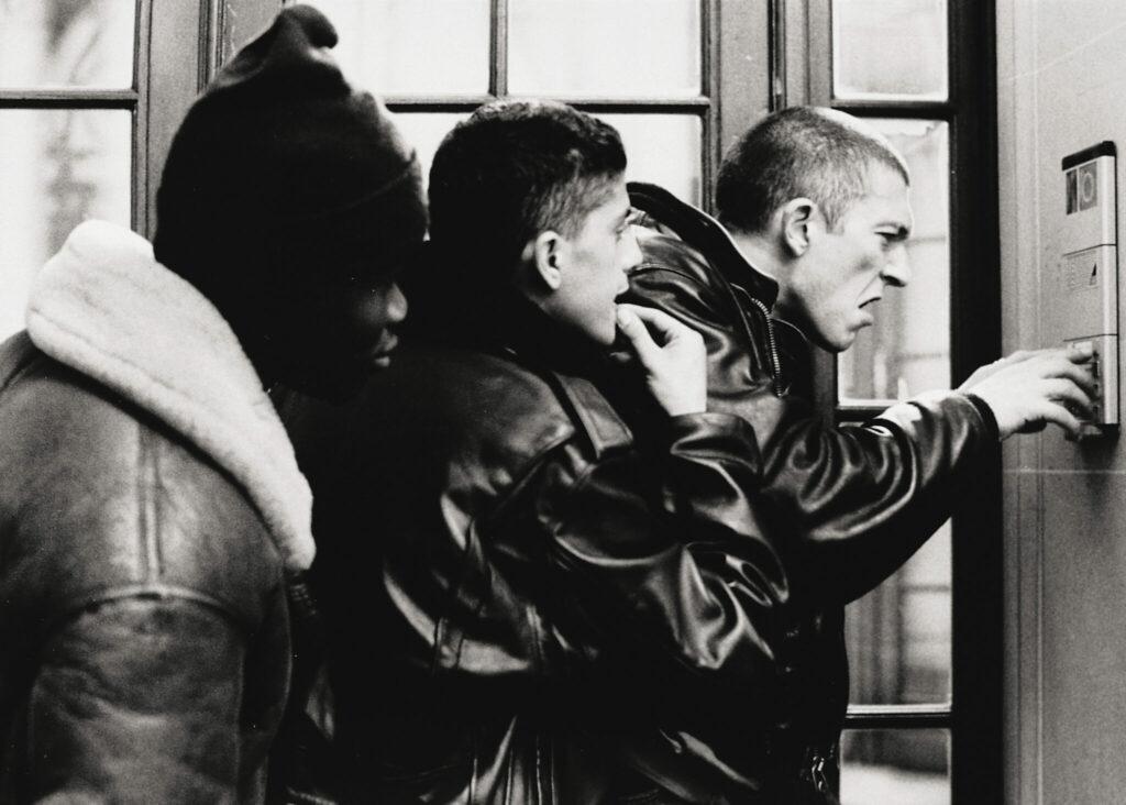 Hubert, Siad und Vinz stehen genervt vor der Gegensprechanlage an der Haustür eines Wohnhauses - Hass