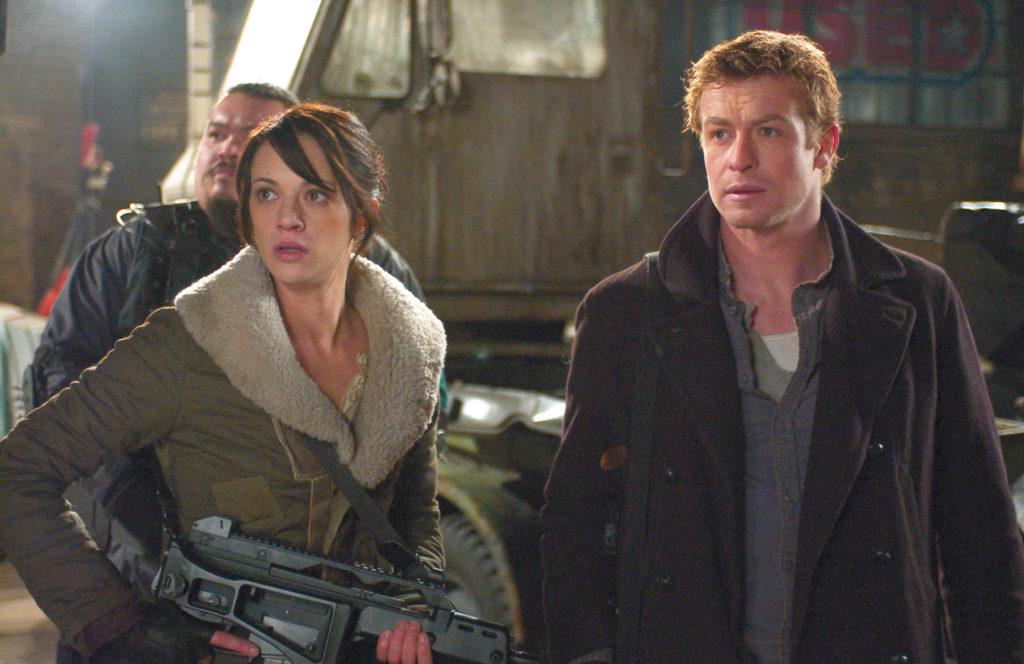 Simon Baker als Riley und Asia Argento als Slack stehen bewaffnet Seite an Seite in Land Of The Dead