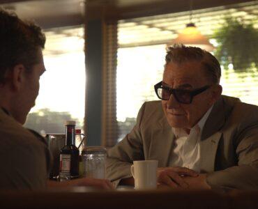 Meyer Lansky, gespielt von Harvey Keitel, sitzt dem Autor David Stone, gespielt von Sam Worthington, gegenüber und erzählt seine Lebensgeschichte. Seine Augen sind hinter einer Sonnebrille verborgen.