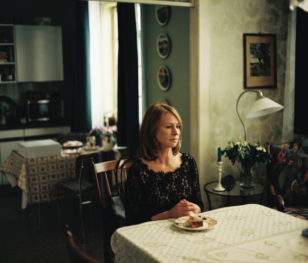 Corinna Harfouch sitzt als Lara alleine an einem Tisch vor einem Stück Kuchen